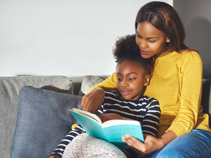mom and daughter reading  book